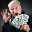 Happy elderly with fan of money — Stock Photo