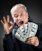 Happy elderly with fan of money — Stock Photo