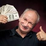 Elderly man showing fan of money — Stock Photo