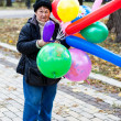 An elderly woman with balloons - Stock Photo
