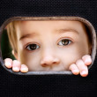 Kid spying through the hole - Stock Photo