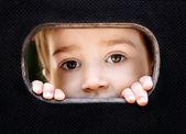 Kid spying through the hole — Stock Photo