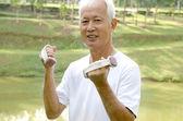 Senior man using dumbells — Stock Photo