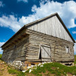 Wooden house and mountains - Stock Photo