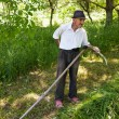 Old man sharpening his scythe — Stock Photo #11529327