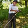 Old man sharpening his scythe — Stock Photo