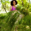 Photo: Young woman piling up mowed grass