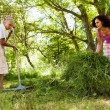 Senior woman piling up mowed grass — ストック写真