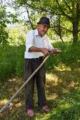 Old man sharpening his scythe — Stock Photo