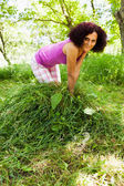 Young woman piling up mowed grass — Stock Photo