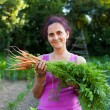 Young woman farmer holding vegetables - Stock Photo