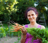 Young woman farmer holding vegetables — Stock Photo