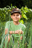 Boy in a lawn of onions — Stock Photo