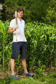 Young farmer near a corn field — Stok fotoğraf