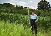 Senior farmer with scythe — Stock Photo