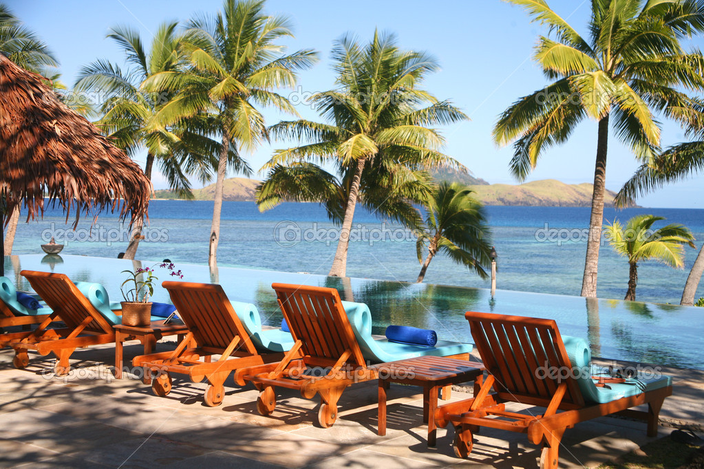 Fiji with palm trees, sea, pool and deck chairs — Stock Photo #11788660