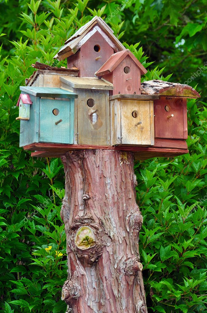 Stacked birdhouses on top of tree stump — Stock Photo #11547655