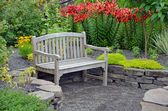 Wooden bench in lily garden — Stock Photo