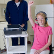 Stock Photo: School nurse giving hearing test