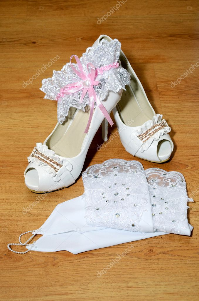 White shoes gloves and a garter for the bride on wooden background — Stock Photo #10964021