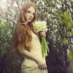 Portrait une belle jeune femme avec des fleurs dans le jardin — Photo #11267090