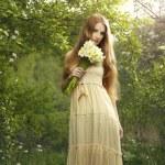 Portrait une belle jeune femme avec des fleurs dans le jardin — Photo #11267094