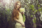 Portrait a beautiful young woman with flowers in the garden — Stock Photo