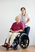 Senior woman and aid or nurse — Stock Photo