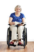 Senior disabled woman in wheelchair with book — Stock Photo