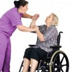 Nurse assaulting senior woman in wheelchair — Stock Photo