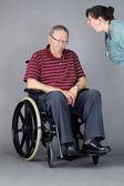 Sad senior man in wheelchair being shouted at by nurse — Stock Photo