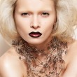Fashion halloween looking. Big hairstyle, fantasy jewellery and carnival style. Beautiful model with dark lips, pins necklace and without eyebrow — Stock Photo #11152754