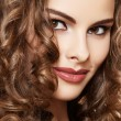 Stock Photo: Lovely model with shiny volume curly hair. Pin-up style