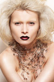 Fashion halloween looking. Big hairstyle, fantasy jewellery and carnival style. Beautiful model with dark lips, pins necklace and without eyebrow — Stock Photo