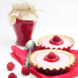 Raspberry tarts and jar of raspberry jam - Stockfoto
