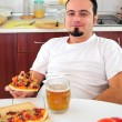 Young man in kitchen with homemade pizza - Stock Photo