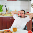 Young man in kitchen enjoying homemade pizza - ストック写真