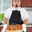 Young man in kitchen with homemade pizza — Photo