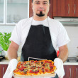 Young man in kitchen with homemade pizza — Stock Photo