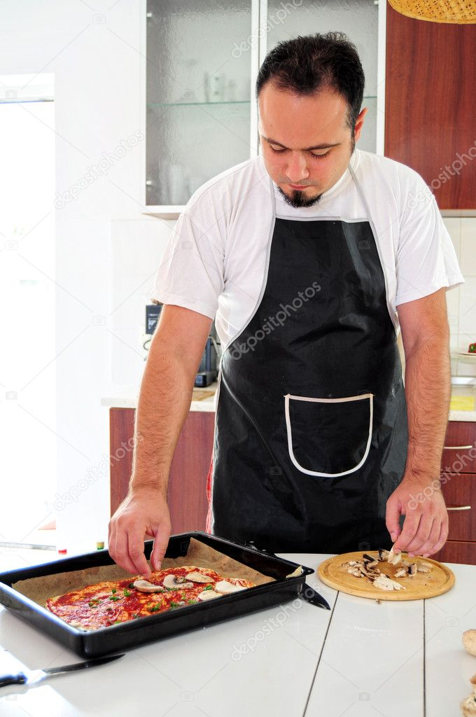 Young man in apron in kitchen preparing pizza — Stock Photo #12147607