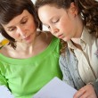 Girl doing homework with her mom — Stockfoto