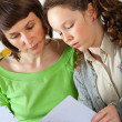 Girl doing homework with her mom — Stok fotoğraf