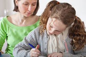 Girl doing prework with her mom — Stock Photo