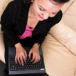 Happily working - young business woman with laptop - top view — Stock Photo