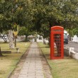 Red Phone Booth by Sidewalk Through Park — Stock Photo