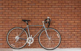 Old Bicycle Leaning Against Red Brick Wall — Stock Photo