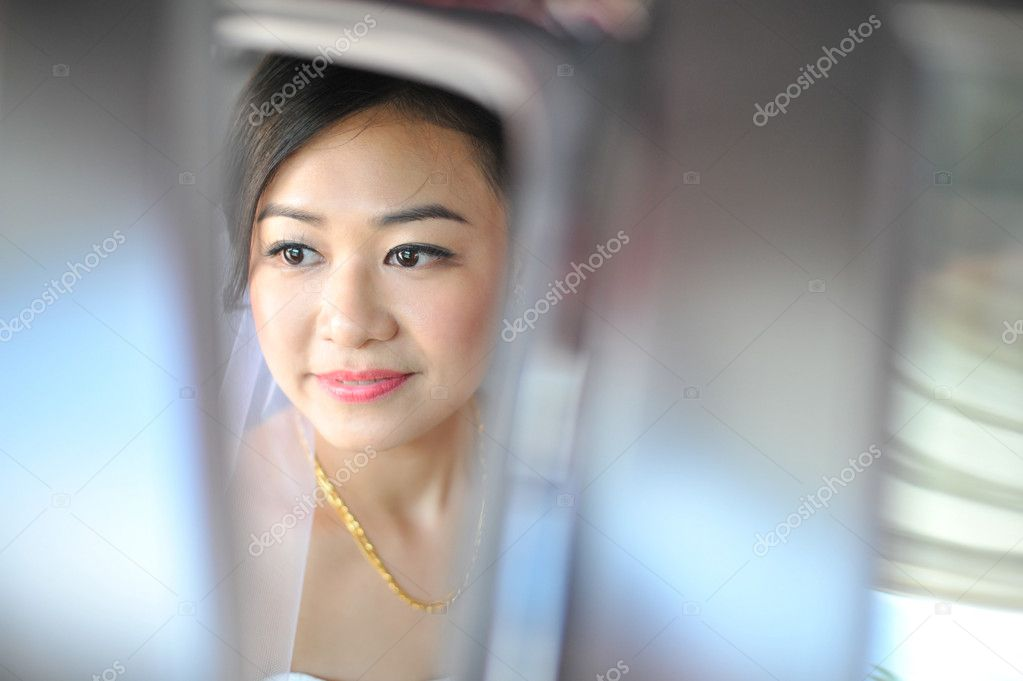 Asian bride looks out of the car  Stock Photo #11189644