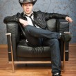 Young cowboy sitting in leather chair in the interior — Stock Photo