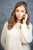 Portrait of a girl with a telephone against the backdrop of a re — Stock Photo