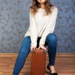 beautiful young girl sitting on an old brown suitcase in the int — Stock Photo